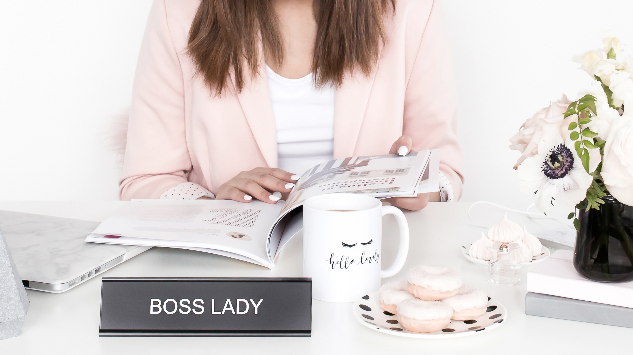 An entrepreneur in a pink blazer, looking over print material as her own boss today.